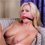 Sexy blond milf bound and gagged on her couch.
